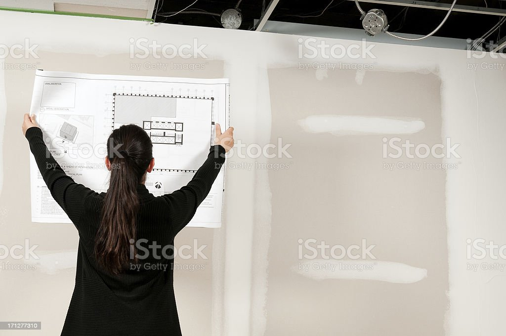 Designer Reviewing Construction Plans in an Unfinished Room stock photo