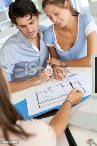 466848706 istock photo Designer showing a couple a blueprint in a blue binder 154038886
