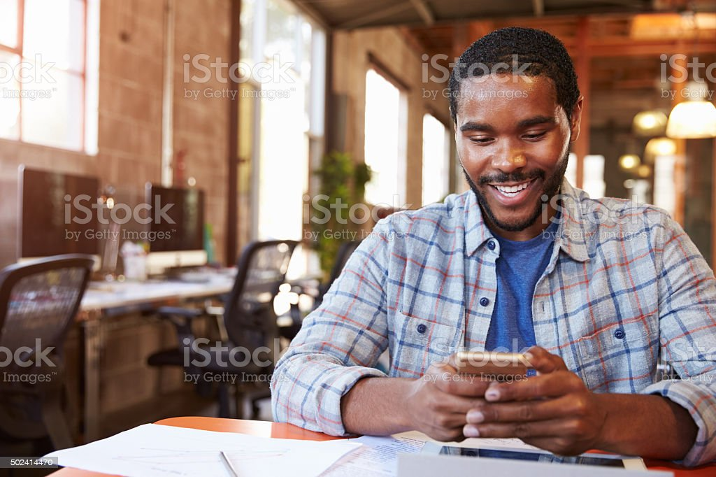 Designer Sitting At Meeting Table Texting On Mobile Phone stock photo