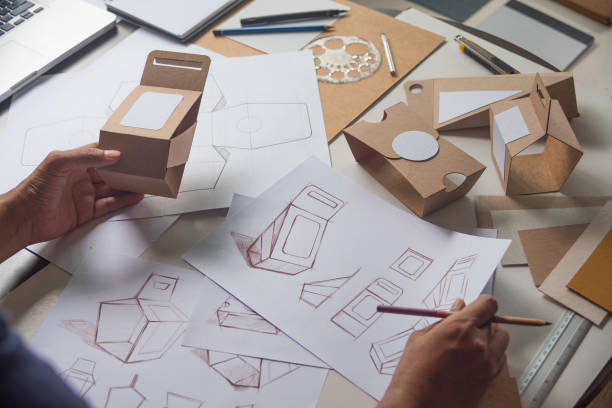 designer sketching drawing design brown craft cardboard paper product eco packaging mockup box development template package branding label . designer studio concept . - packaging foto e immagini stock