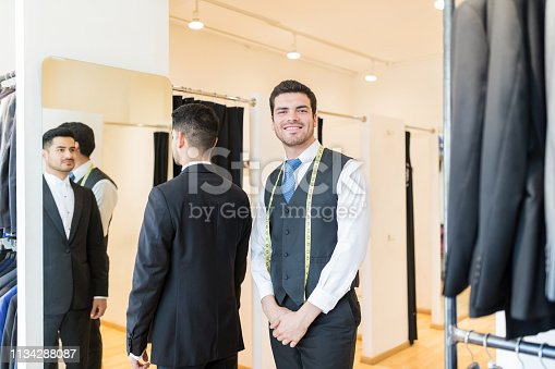 istock Designer Standing By Client Wearing Suit At Rental Store 1134288087