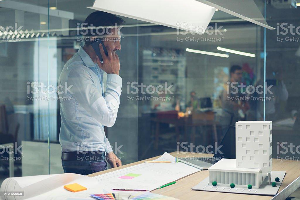 Designer talking on smart phone in office. stock photo