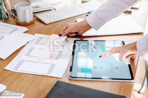 istock UX designer team using tablet designing smartphone prototype or application layout at office desk. 1162159158