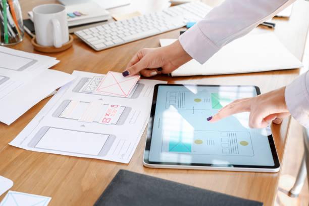 Equipo de diseñadores de UX que utiliza el diseño de tabletas para el diseño de prototipos de smartphone o el diseño de aplicaciones en el escritorio de la oficina. - foto de stock