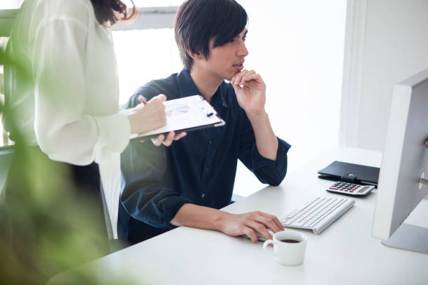 Designer to adjust design while consulting with manager stock photo