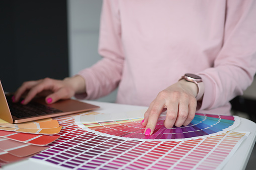 Designer typing on laptop keyboard and choosing color in palette closeup. Work in design studio concept