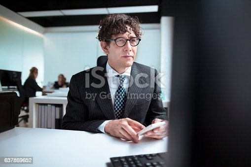 660311448 istock photo Designer using smart phone and computer in office 637869652