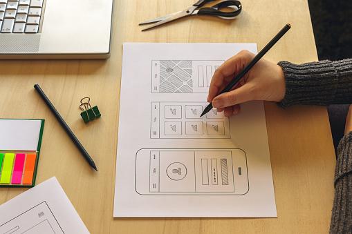 Designer wireframing a mobile App on wooden desk