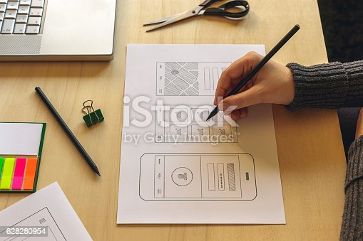 995213208 istock photo Designer wireframing a mobile App 628280954
