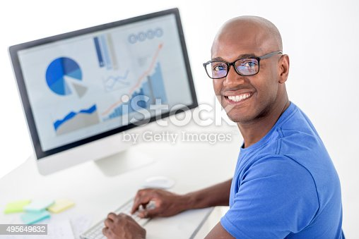 African American man working at the office and using a computer while wearing glasses - isolated over white