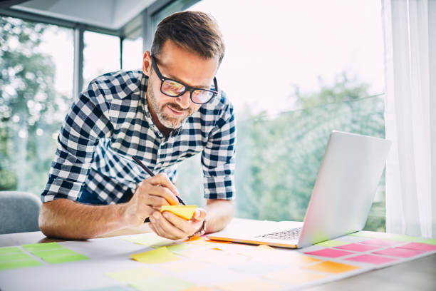 Designer working from home office taking notes stock photo