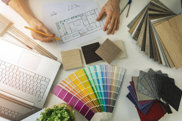 designer working in office doing furniture and flooring material selection from samples for home interior design project. top view stock photo