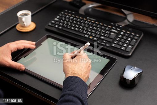 Designer Working On Digital Tablet Using Stylus Pen on Work Desk