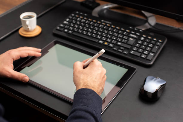 designer working on digital tablet using stylus pen on work desk - electronics industry stock pictures, royalty-free photos & images