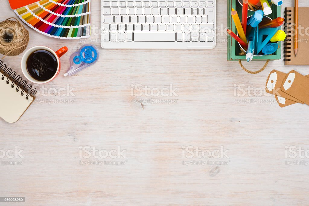 Designer workspace top view with essential elements on wooden board stock photo