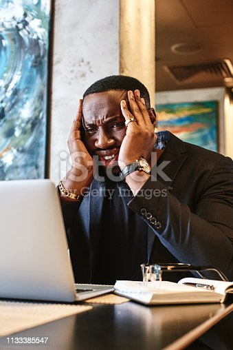 istock Designer worry about deadline of new project. Man hold head by two hands and look in laptop with pensive expression. Manager seek solution to pass the job in time. 1133385547