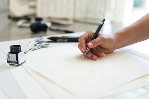 designer writing logo. designers hand holding a pen and writing logo. woman designer at work in her office working on project - logo design stock photos and pictures