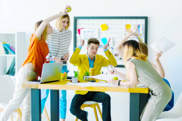 Designers and architects working at office Young man boss is shocked at meeting with angry aggressive women colleagues. Architects interior designers emotionally discuss the design-project in light creative office. Conflict at job concept. shock tactics stock pictures, royalty-free photos & images
