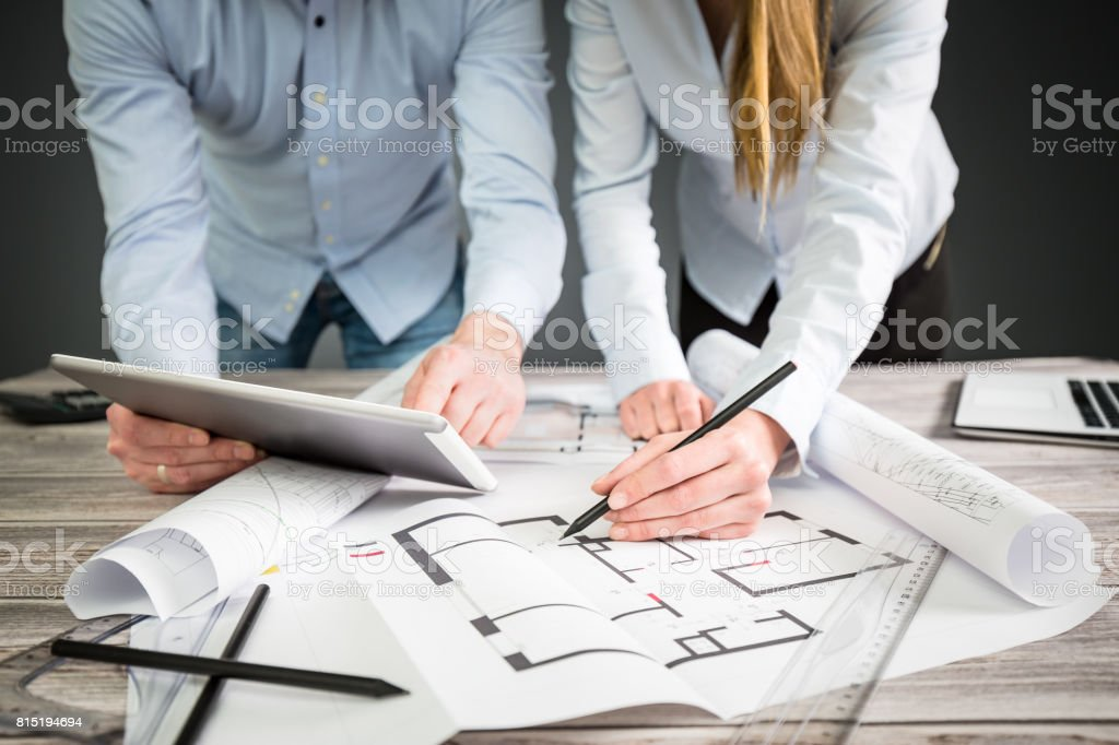 Designer diskutieren die Skizzen im Inneren des Hauses. - Lizenzfrei Arbeiten Stock-Foto