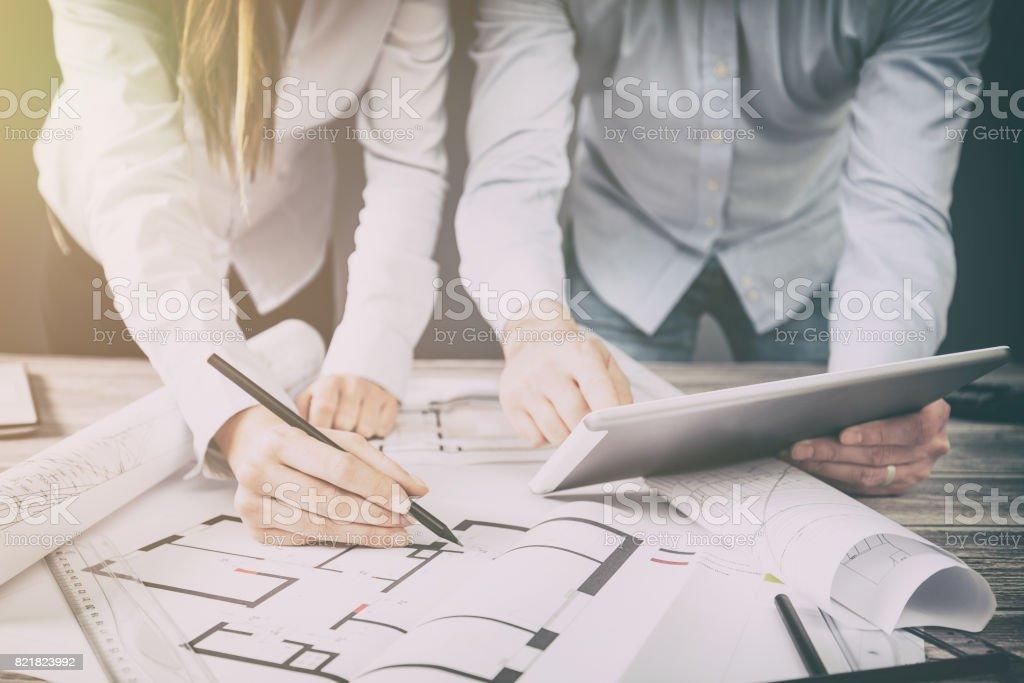 Designer diskutieren die Skizzen im Inneren des Hauses. – Foto