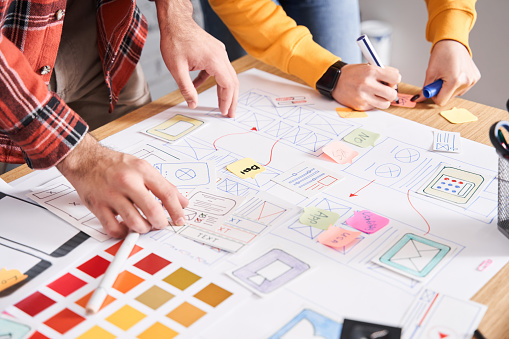 Top view of the UX designers drawing the application on paper. Mobile app template, web designer draws apps, application template for smartphone, tablet application mockup on paper, app creation concept