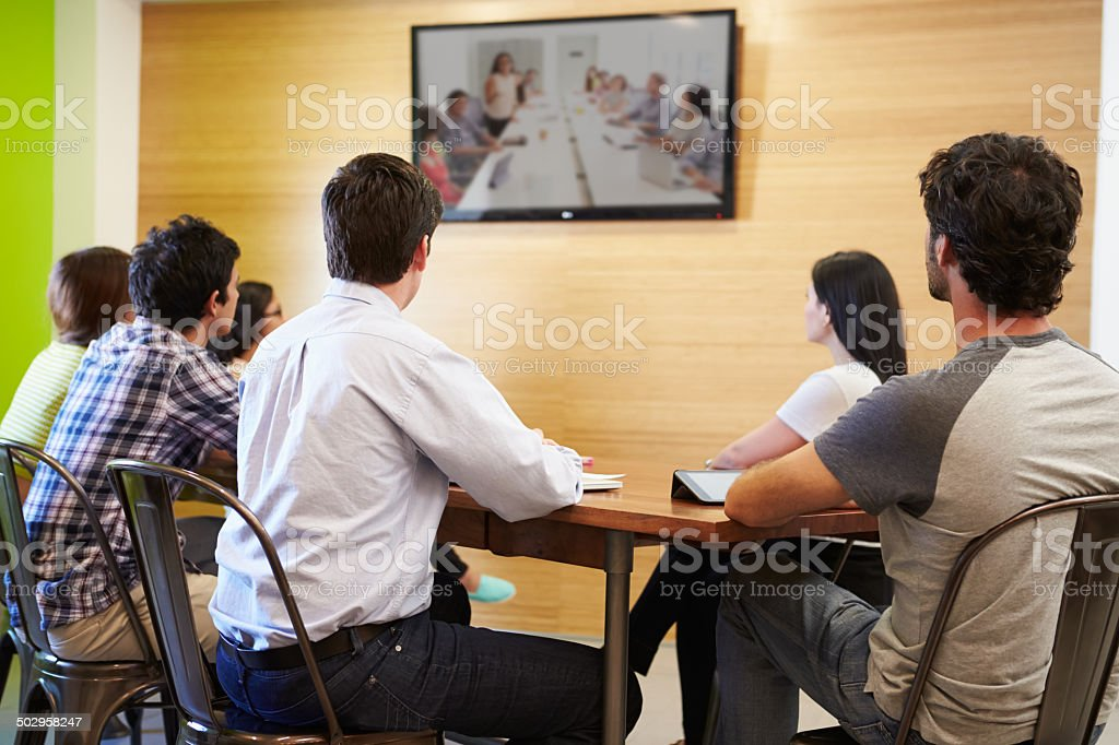 Designers Sitting Around Table In Meeting Looking At Screen stock photo