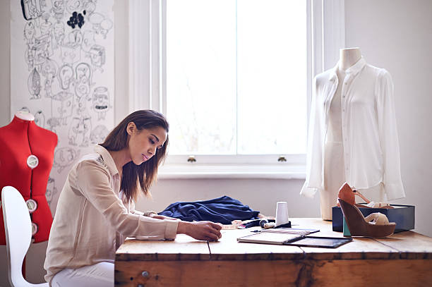 Designing her new clothing line A young fashion designer making sketches in her office fashion designer stock pictures, royalty-free photos & images