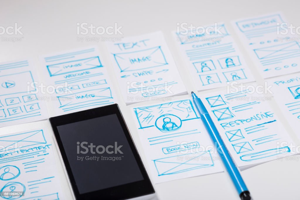 Designing interface for mobile digital experience. Desk with smartphone and designer sketches for mobile app - foto de stock