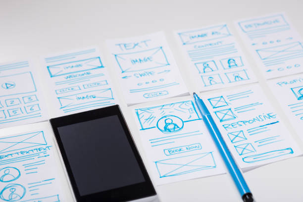 Designing interface for mobile digital experience. Desk with smartphone and designer sketches for mobile app stock photo