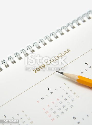 istock Desk calendar and yellow pencil on white background. 1067688876