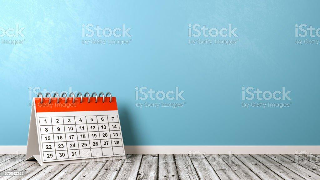 Desk Calendar on Wooden Floor Against Wall stock photo