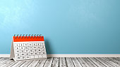 Desk Calendar on Wooden Floor Against Wall
