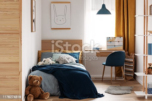istock Desk, chair and single bed with blue bedding in cozy bedroom interior for children 1176274319