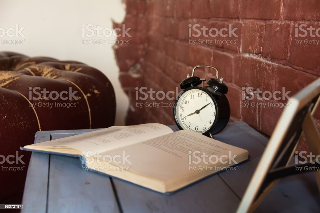 Desk clock with an open book on a wooden table against a brick wall background stock photo