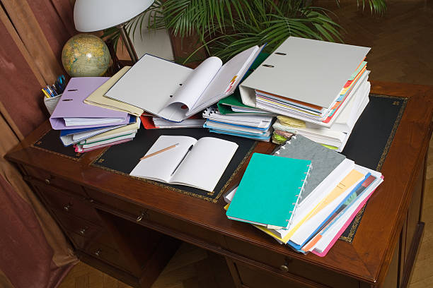Desk, cluttered with binders and paper stock photo