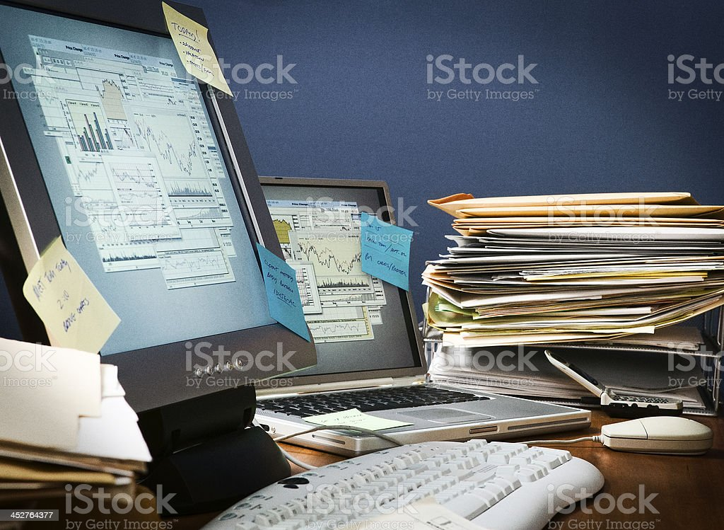 Desk cluttered with paperwork and sticky notes stock photo