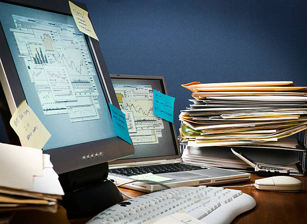 Desk cluttered with paperwork and sticky notes Office desk cluttered with paperwork, post-it-notes and files. messy home office stock pictures, royalty-free photos & images