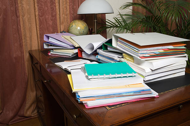 Desk, cluttered with stuff Cluttered desk of an overworked secretary or student. messy home office stock pictures, royalty-free photos & images