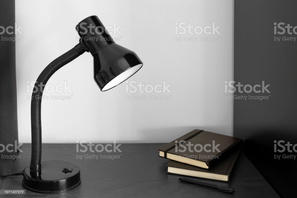 Black desk lamp pen and two note books set on black table and white...