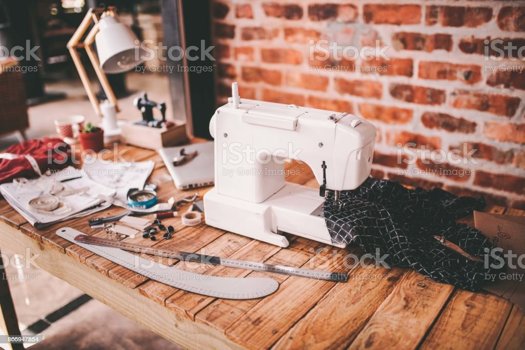 Desk of fashion designer with sewing machine and tools stock photo