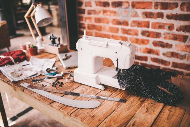 desk of fashion designer with sewing machine and tools - sewing machine needle stock photos and pictures