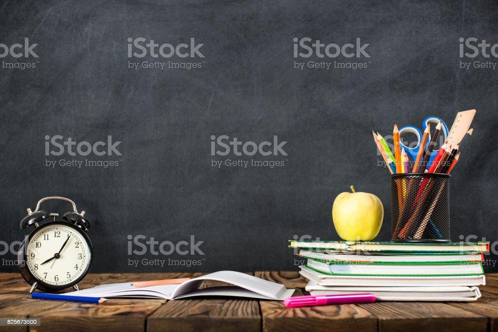 Escritorio del estudiante, reloj despertador, libros y lápices foto de stock libre de derechos