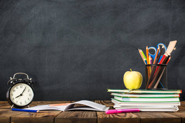 desk of student, alarm clock, books and pencils - back to school stock photos and pictures