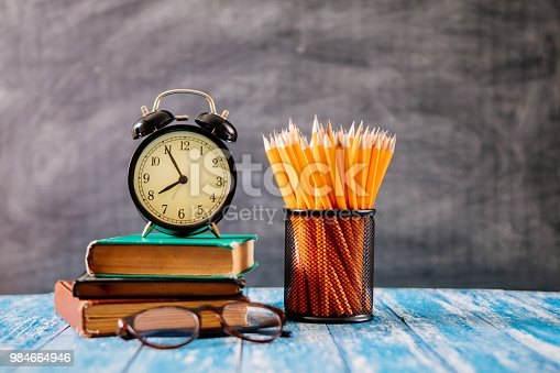 istock Desk Of Student, Alarm Clock, Books and Pencils 984664946