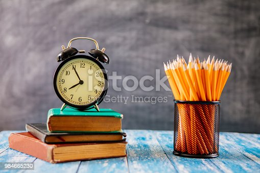 istock Desk Of Student, Alarm Clock, Books and Pencils 984665230