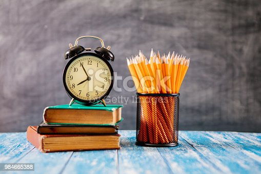 istock Desk Of Student, Alarm Clock, Books and Pencils 984665388