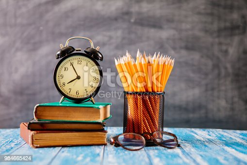 istock Desk Of Student, Alarm Clock, Books and Pencils 984665424