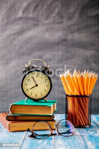 istock Desk Of Student, Alarm Clock, Books and Pencils 984665548