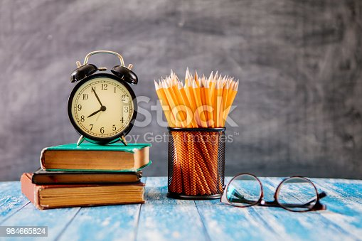 istock Desk Of Student, Alarm Clock, Books and Pencils 984665824