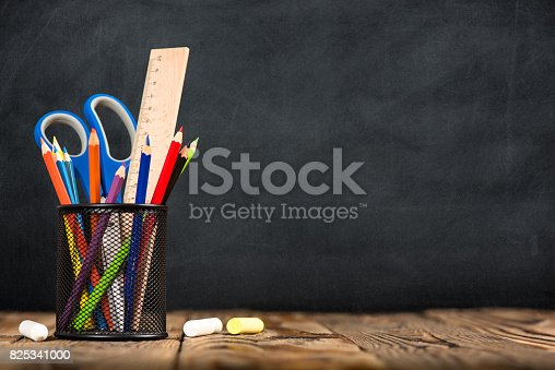 istock Desk Of Student, Pencils In Metal Holder On Blackboard Background 825341000